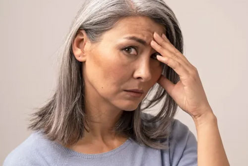 Mature woman touching her head stock picture